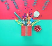 Rote Geschenkbox mit bunten Parteieinzelteilen Stockfotos