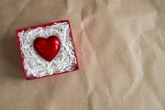 Rote Geschenkbox mit Herzen bis zum Valentinstag auf Kraftpapier Geben des Herzliebeskonzeptes, Kopienraum stockfotografie