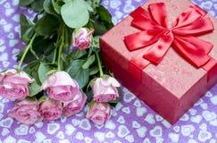 Rote Geschenkbox und Blumenstrauß von Rosen Stockbild