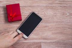 Rote Geschenkbox und menschliche Hand drückt den Knopf von Smartphone mit Kopienraum lizenzfreie stockbilder