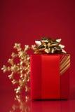 Rote Geschenkbox und Weihnachtsschneeflocke auf rotem Hintergrund Lizenzfreies Stockfoto