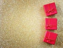 Rote Geschenkboxen auf Funkelngoldhintergrund Lizenzfreie Stockfotos