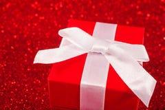 Rote Geschenkboxen auf Funkelnrothintergrund Stockbild