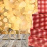 Rote Geschenkboxen und hölzerne Zahl von 2017 auf einem Bretterboden und einem gol Stockfotos
