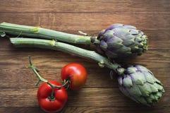 Rote geschmackvolle süße italienische Tomaten und Artischocken auf dem hölzernen Ba stockfoto