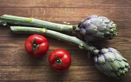 Rote geschmackvolle süße italienische Tomaten und Artischocken auf dem hölzernen Ba stock abbildung