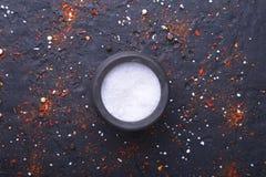 Rote Gewürze, Salz und Pfeffer auf schwarzem Marmor Schwarzer abstrakter Hintergrund Beschneidungspfad eingeschlossen Stockbilder