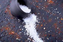 Rote Gewürze, Salz und Pfeffer auf schwarzem Marmor Schwarzer abstrakter Hintergrund Beschneidungspfad eingeschlossen Stockbild