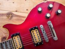 Rote Gitarre der Weinlese auf alter Holzoberfläche Lizenzfreies Stockfoto