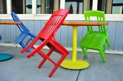 Rote, grüne und blaue Stühle, die auf Tabellen sich lehnen Stockfotografie