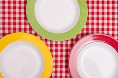 Rote, grüne und gelbe Platte auf einem Stoff Stockbilder
