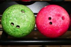 Rote grüne Nahaufnahmereihe der Bowlingspielkugeln Stockbild