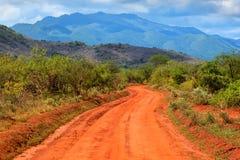 Rote Grundstraße und Savanne. Tsavo West, Kenia, Afrika Lizenzfreies Stockfoto