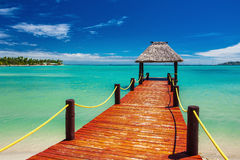 Rote hölzerne Anlegestelle, die auf tropischen Ozean auf Fidschi-Insel verlängert stockbilder