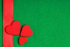Rote hölzerne dekorative Herzen auf grünem Stoffhintergrund Stockfotografie