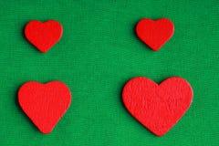 Rote hölzerne dekorative Herzen auf grünem Stoffhintergrund Stockbild