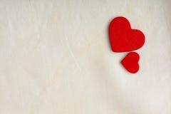 Rote hölzerne dekorative Herzen auf weißem Stoffhintergrund. Stockbilder