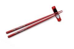 Rote hölzerne Essstäbchen und Essstäbchenhalter auf weißem Hintergrund Stockbild