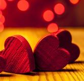 Rote hölzerne Herzen mit Lichtern im Hintergrund lizenzfreies stockbild