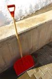 Rote hölzerne Schaufel, die an der Wand sich lehnt Stockbilder
