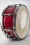 Rote hölzerne Schnarrtrommel lokalisiert auf einem weißen Hintergrund. Rockmusik lizenzfreie stockbilder