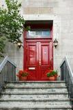 Rote hölzerne Tür mit zwei Laternen Stockfotos