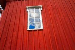 Rote hölzerne Wand und ein Fenster mit den Wolken reflektiert Lizenzfreies Stockfoto