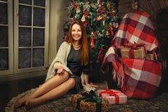 Rote Haarfrau, die im Studio mit Weihnachtsdekoration aufwirft Stockbild