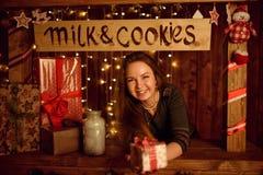 Rote Haarfrau, die im Studio mit Weihnachtsdekoration aufwirft Stockfoto