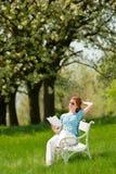 Rote Haarfrau, die weißes Buch auf einer Bank liest Lizenzfreies Stockfoto