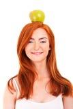 Rote Haarfrau mit grünem Apfel auf ihrem Kopf Stockfotografie