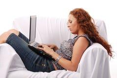 Rote Haarschönheit auf Sofa lizenzfreie stockbilder