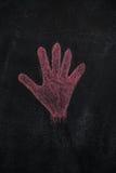 Rote Handform auf schwarzer Tafel Stockbilder