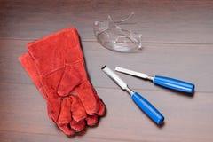 Rote Handschuhe, Gläser und blaue Meißel Lizenzfreie Stockbilder