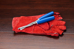 Rote Handschuhe und blaue Meißel auf hölzernem Fußboden Lizenzfreies Stockfoto