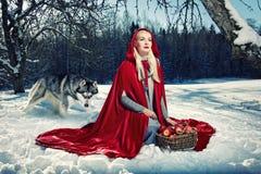 Rote Haube und ein Wolf hinter ihr. Lizenzfreie Stockfotografie
