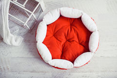 Rote Haustiermatratze im Raum mit Käfig Lizenzfreies Stockbild