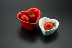 Rote Herz-förmige Schüsseln und blaue Herz-förmige Schüsseln und rote Tomaten Lizenzfreie Stockfotos