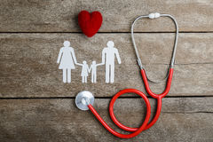 Rote Herz-, Stethoskop- und Papierkettenfamilie auf Holztisch Stockbilder