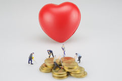 Rote Herz- und Unschärfemünzenstapel mit Miniatur stockbilder