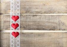 Rote Herzen auf altem hölzernem Hintergrund Stockfotos