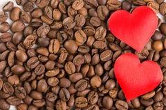 Rote Herzen auf dem Stapel von Kaffeebohnen Lizenzfreies Stockfoto