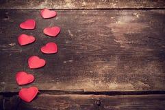 Rote Herzen auf den alten dunklen Brettern Stockfotografie