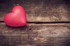 Rote Herzen auf den alten dunklen Brettern Stockbilder