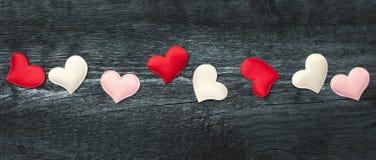 Rote Herzen auf den dunklen Brettern Lizenzfreies Stockfoto