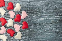 Rote Herzen auf den dunklen Brettern Stockfotografie