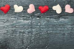 Rote Herzen auf den dunklen Brettern Stockbild