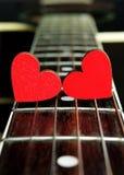 Rote Herzen auf den Schnüren einer Gitarre Herzen sind ein Symbol der Liebe Lizenzfreie Stockfotografie