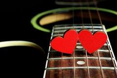 Rote Herzen auf den Schnüren einer Gitarre Herzen sind ein Symbol der Liebe Valentinsgruß `s Tag Lizenzfreie Stockfotos