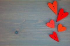 Rote Herzen auf grauem hölzernem Hintergrund Knopfliebe Stockbild
